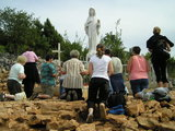 Women kneeling before the Statue of Queen of Peace at Apparition Hill